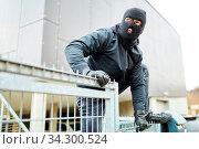 Vermummter Einbrecher klettert über einen Zaun beim Einbruch. Стоковое фото, фотограф Zoonar.com/Robert Kneschke / age Fotostock / Фотобанк Лори