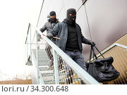Einbrecher flüchten über Treppe aus Büro mit einer Tasche voller Beute. Стоковое фото, фотограф Zoonar.com/Robert Kneschke / age Fotostock / Фотобанк Лори
