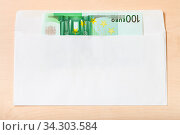 Single one hundred euro note in open mail envelope on wooden table. Стоковое фото, фотограф Zoonar.com/Valery Voennyy / easy Fotostock / Фотобанк Лори