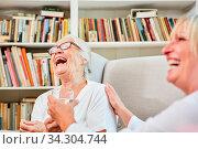 Altenpflegerin und glückliche Senior Frau lachen zusammen im Seniorenheim. Стоковое фото, фотограф Zoonar.com/Robert Kneschke / age Fotostock / Фотобанк Лори