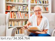 Neugierige Seniorin in der Bücherei liest ein Buch für Wissen und Weiterbildung. Стоковое фото, фотограф Zoonar.com/Robert Kneschke / age Fotostock / Фотобанк Лори