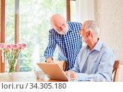 Zwei Senioren als Rentner am Laptop Computer helfen sich beim E-Learning. Стоковое фото, фотограф Zoonar.com/Robert Kneschke / age Fotostock / Фотобанк Лори