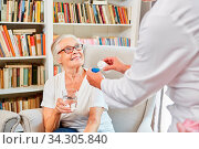 Krankenpflegerin verteilt Medikamente an Senior Frau im betreuten Wohnen. Стоковое фото, фотограф Zoonar.com/Robert Kneschke / age Fotostock / Фотобанк Лори