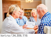 Ärztin betreut Senioren in einer Therapie Sitzung und zeigt ihm ein Diagramm. Стоковое фото, фотограф Zoonar.com/Robert Kneschke / age Fotostock / Фотобанк Лори