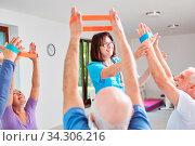 Reha Therapeutin gibt Senioren Hilfestellung in einem Ergotherapie Kurs. Стоковое фото, фотограф Zoonar.com/Robert Kneschke / age Fotostock / Фотобанк Лори