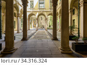 Beautiful inner courtyard of an old building in the historical center of Milan, at the intersection of streets Via dei Giardini and Via Borgonuovo. City of Milan, region of Lombardy, Italy, Europe. (2018 год). Редакционное фото, фотограф Bala-Kate / Фотобанк Лори