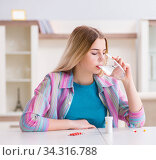 Woman taking pills to cope with pain. Стоковое фото, фотограф Elnur / Фотобанк Лори