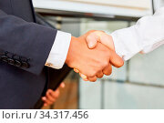 Zwei Geschäftsleute geben sich die Hand als Konzept für Kooperation und Vertrag. Стоковое фото, фотограф Zoonar.com/Robert Kneschke / age Fotostock / Фотобанк Лори