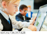Business Kinder in Computer Klasse arbeiten an Tablet PCs im Unterricht. Стоковое фото, фотограф Zoonar.com/Robert Kneschke / age Fotostock / Фотобанк Лори