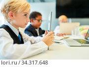 Junge als Schüler mit Tablet Computer in einer Klasse oder im Business Meeting. Стоковое фото, фотограф Zoonar.com/Robert Kneschke / age Fotostock / Фотобанк Лори