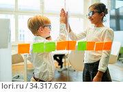 Zwei Kinder als Geschäftsleute geben sich zur Motivation ein High Five im Büro. Стоковое фото, фотограф Zoonar.com/Robert Kneschke / age Fotostock / Фотобанк Лори