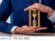 Young male employee in time management concept. Стоковое фото, фотограф Elnur / Фотобанк Лори