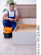 Young male contractor installing furniture at home. Стоковое фото, фотограф Elnur / Фотобанк Лори