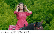 Young woman in pink dress sitting on a horse. Стоковое видео, видеограф Константин Шишкин / Фотобанк Лори