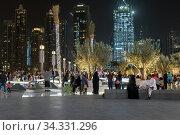 Dubai, UAE - April 8. 2018. Tourists on square at fountain in front of Dubai Mall. Редакционное фото, фотограф Володина Ольга / Фотобанк Лори