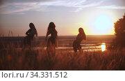 Three young women doing aerobic dance on sunset field. Стоковое видео, видеограф Константин Шишкин / Фотобанк Лори