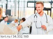 Erfolgreicher junger Arzt beim Hände schütteln als Zeichen für Gratulation oder Begrüßung. Стоковое фото, фотограф Zoonar.com/Robert Kneschke / age Fotostock / Фотобанк Лори