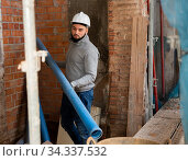 Guy working with plastic pipes at building site. Стоковое фото, фотограф Яков Филимонов / Фотобанк Лори