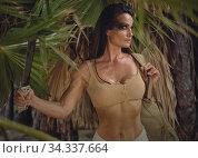 Female holding machete posing on wild nature of palm trees forest. Spirit of adventure. Survivor woman concept. Стоковое фото, фотограф Alexander Tihonovs / Фотобанк Лори
