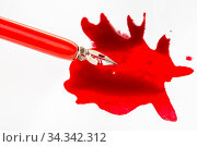 Above view of nib in red dip pen over red ink blot on white paper. Стоковое фото, фотограф Zoonar.com/Valery Voennyy / easy Fotostock / Фотобанк Лори