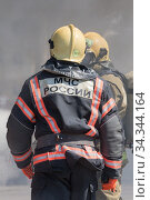 Back view with emblem Emercom of Russia on uniform firefighters of Ministry of Civil Defence, Emergencies and Disaster Relief of Russian MChS (2019 год). Редакционное фото, фотограф А. А. Пирагис / Фотобанк Лори