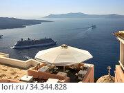 Oia, Santorini, Greece, August 21, 2013: A cozy cafe with beautiful views of the mountains and the blue sea. Редакционное фото, фотограф Олег Белов / Фотобанк Лори