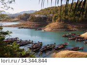 Khao Sok, Thailand, February 07, 2020: View of the bay with turquoise water and many wooden boats. Редакционное фото, фотограф Олег Белов / Фотобанк Лори
