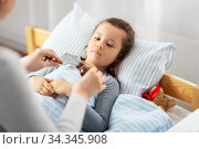 mother pouring cough syrup for sick daughter. Стоковое фото, фотограф Syda Productions / Фотобанк Лори