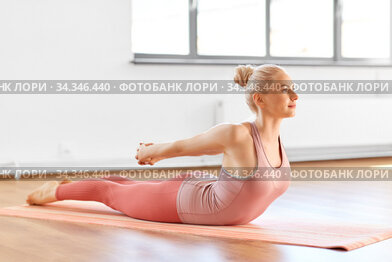 young woman doing yoga bending her back at home
