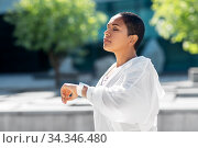young woman with smart watch breathing outdoors. Стоковое фото, фотограф Syda Productions / Фотобанк Лори