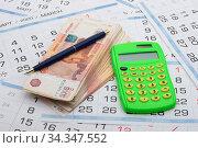На календаре лежат пачка денег, калькулятор и ручка. Стоковое фото, фотограф Иванов Алексей / Фотобанк Лори