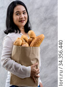 Portrait of asian smile woman housewife holding variety bread in disposable... Стоковое фото, фотограф Zoonar.com/Vichie81 / easy Fotostock / Фотобанк Лори