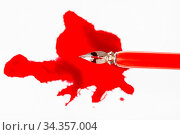Top view of steel nib in red dip pen over red ink blot on white paper. Стоковое фото, фотограф Zoonar.com/Valery Voennyy / easy Fotostock / Фотобанк Лори