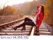 A gorgeous romantic young woman seated down on the railroad tracks... Стоковое фото, фотограф Zoonar.com/Arthur Mustafa / easy Fotostock / Фотобанк Лори