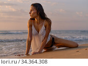 Sexy woman pose on the beach during sunrise. Стоковое фото, фотограф Alexander Tihonovs / Фотобанк Лори