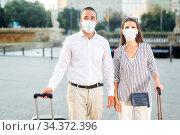 Tourist couple in face masks walking with suitcases. Стоковое фото, фотограф Яков Филимонов / Фотобанк Лори