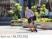 Young casual active sporty businessman in urban city center, wearing shirt and shorts, holding laptop bag, riding to work on electric scooter on a hot summer day. Стоковое фото, фотограф Matej Kastelic / Фотобанк Лори