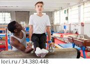 Male coach training teenage boy on gymnastic equipment at acrobatic hall. Стоковое фото, фотограф Яков Филимонов / Фотобанк Лори