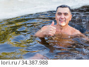 Russia Samara December 2019: a young man is swimming in the ice hole in winter. Редакционное фото, фотограф Акиньшин Владимир / Фотобанк Лори