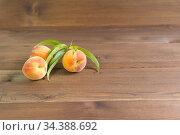 Три персика с листьями на коричневом деревянном столе. Стоковое фото, фотограф Наталья Гармашева / Фотобанк Лори