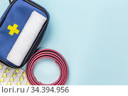 First aid kit for tourism, bandage, medical tourniquet to stop bleeding, pain reliever pills for treatment and assistance in case of accidents in travel hiking on blue background with copy space. Стоковое фото, фотограф Светлана Евграфова / Фотобанк Лори