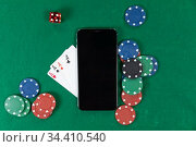 View of a black smartphone, playing cards, a red dice and colorful tokens on plain green surface. Стоковое фото, агентство Wavebreak Media / Фотобанк Лори