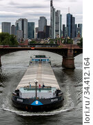 Germany, Frankfurt am Main - Dark clouds over the skyline of the city, in front an inland vessel. Редакционное фото, агентство Caro Photoagency / Фотобанк Лори