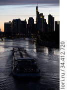 Germany, Frankfurt am Main - inland waterway boat at sunset on the Main and the skyline of the banking district in the city. Редакционное фото, агентство Caro Photoagency / Фотобанк Лори