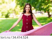 happy woman spreading picnic blanket at park. Стоковое фото, фотограф Syda Productions / Фотобанк Лори