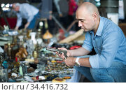 Adult man is looking antiquariat at the market of old things. Стоковое фото, фотограф Яков Филимонов / Фотобанк Лори