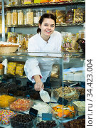 Female merchant is pouring on sweets into bag. Стоковое фото, фотограф Яков Филимонов / Фотобанк Лори