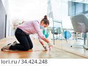 Frau markiert Boden mit Klebeband fürs Abstand halten im Business... Стоковое фото, фотограф Zoonar.com/Robert Kneschke / age Fotostock / Фотобанк Лори