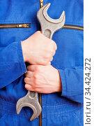 Arbeiter im Blaumann hält einen Doppelmaulschlüssel. Стоковое фото, фотограф Zoonar.com/Robert Kneschke / age Fotostock / Фотобанк Лори