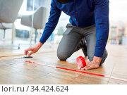 Business Mann markiert Fußboden im Büro mit Klebeband als Maßnahme... Стоковое фото, фотограф Zoonar.com/Robert Kneschke / age Fotostock / Фотобанк Лори